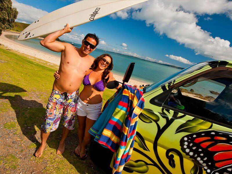 Couple holding a surfboard next to a campervan