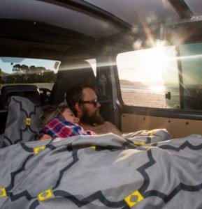 Queen size bed inside a campervan