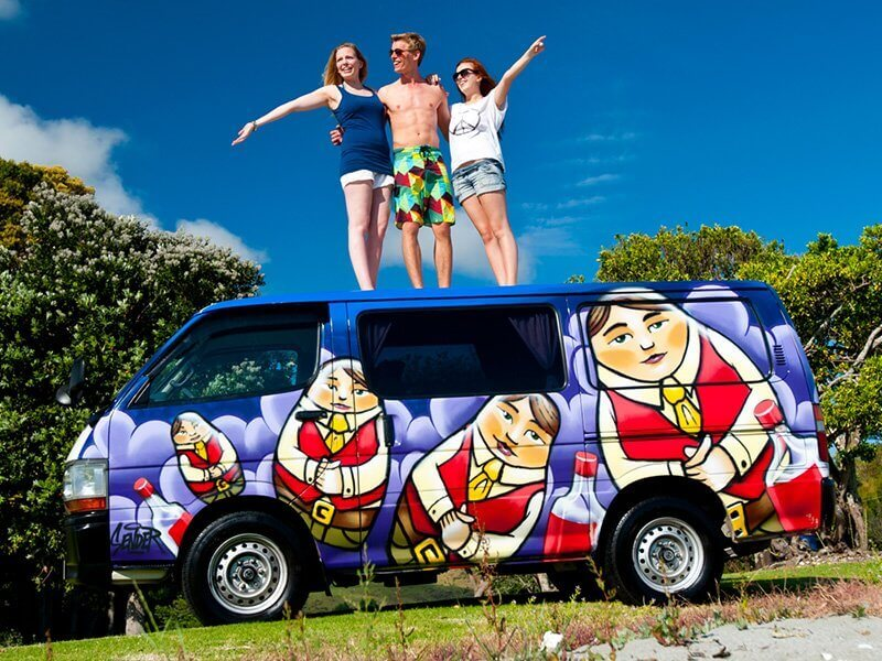 Travellers on top of a Escape Rentals campervan