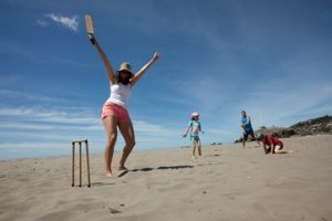 family_playing_cricket_on_sumner_beach